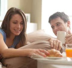 24883572 - beautiful smiling young couple having breakfast in bed